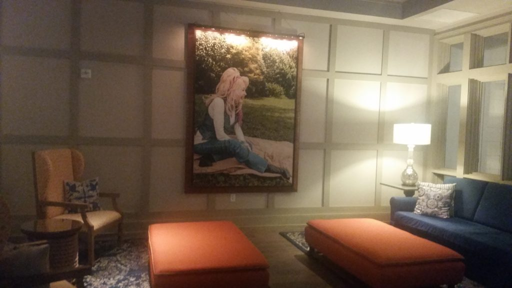 Lobby with sofas and a large framed photograph of Dolly Parton sitting on the ground smiling.